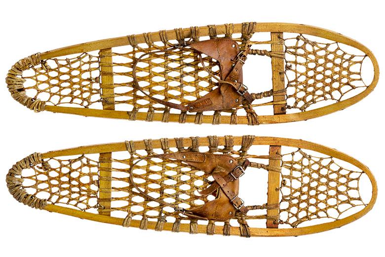 Klassieke houten Bear Paw sneeuwschoenen met lederen bindingen.