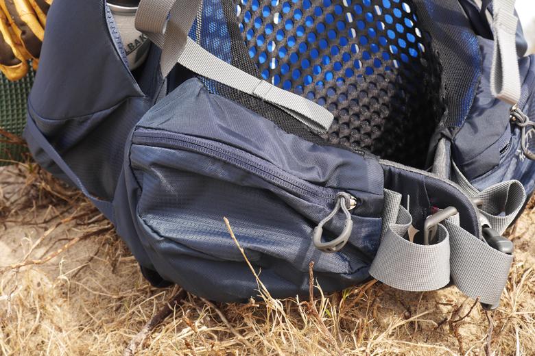 Aan weerszijde van de Osprey Atmos AG 50 vind je twee zakken met rits voor een muesli-reep, een gelletje of een kompas.