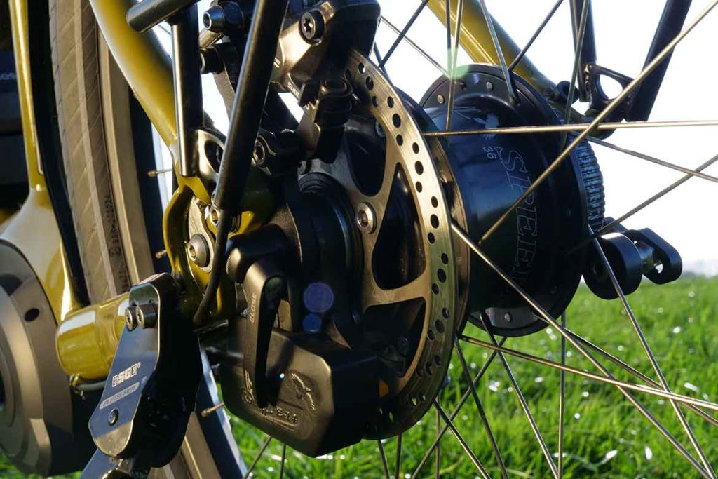 The shifting mechanism is positioned to the left side of the rear wheel.